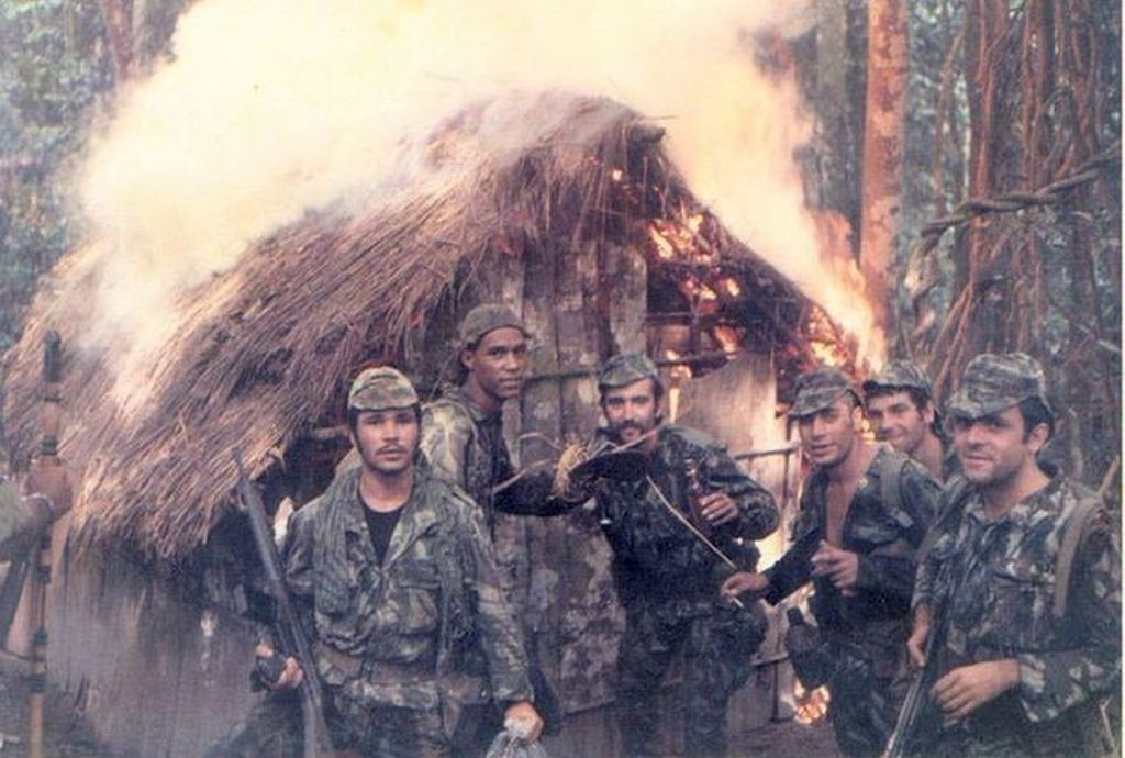 1973_portuguese_soldiers_pose_in_front_of_a_torched_hut_belonging_to_suspected_guerilla_fighters_angolan_war.jpg