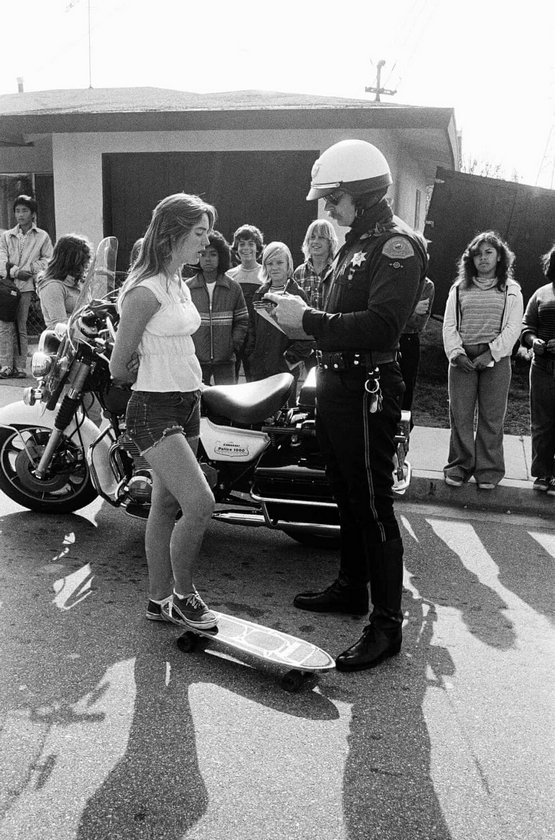 1970s_laurie_piper_getting_ticket_for_skateboarding_in_hermosa_beach_ca.jpeg