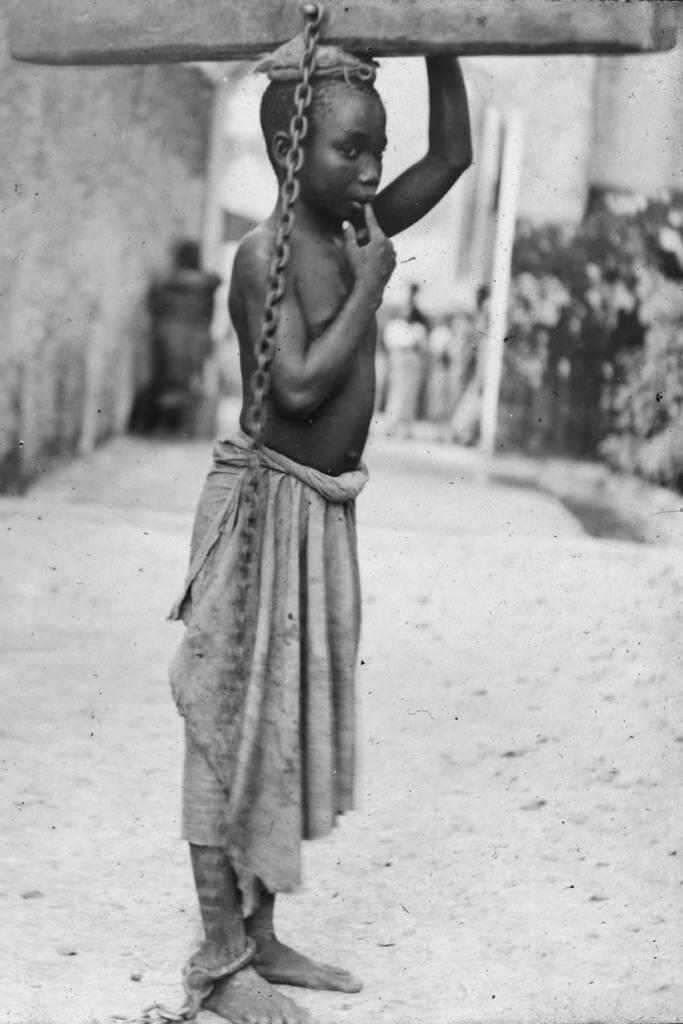 1890. Zanzibári rabszolga fiú. Arab gazdája egy kisebb kihágás miatt bűntette a rönkhöz láncolással. Ezt a fején hordozva a legkönnyebb mozognia..jpg