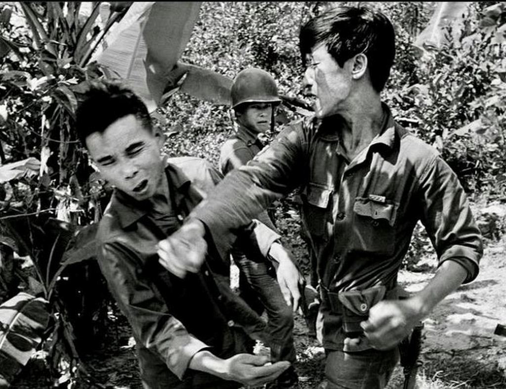 1965_a_south_vietnamese_soldier_punches_a_captured_viet_cong_guerrilla.jpg
