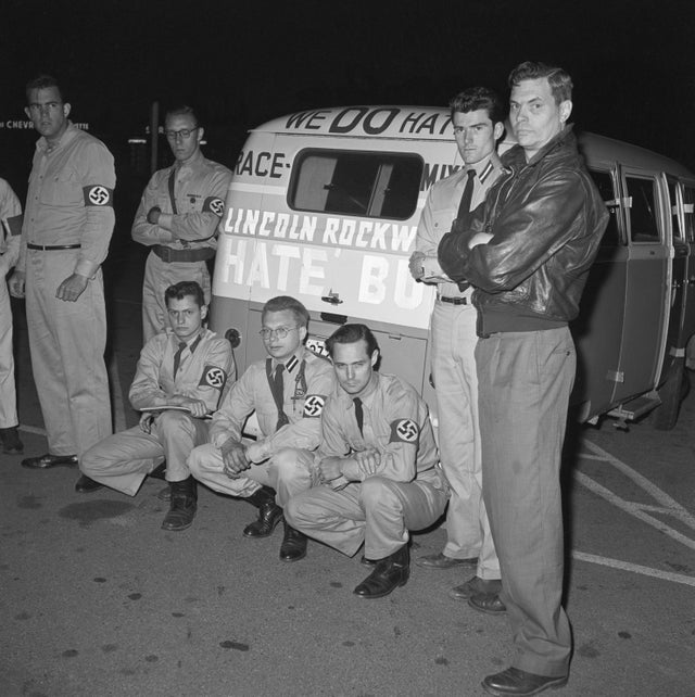 1961_george_lincoln_rockwell_far_right_with_american_nazi_party_members_including_the_man_that_later_killed_him_john_patler_kneeling_left_and_their_volkswagen_hate_bus_in_virginia.jpg