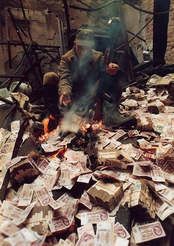 1995_russian_soldier_burning_bank_notes_for_warmth_chechnya.jpg