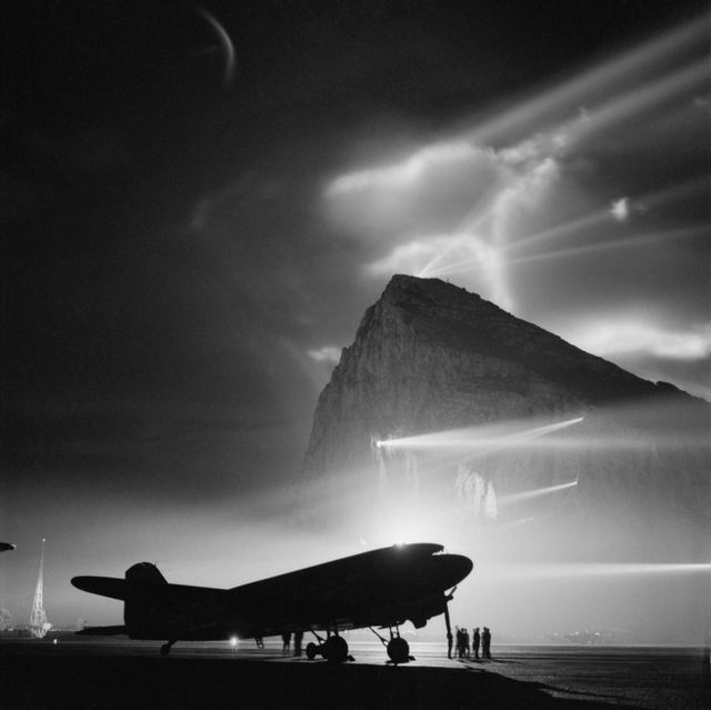 1942_a_douglas_dakota_of_boac_silhouetted_by_night_at_gibraltar_by_the_batteries_of_searchlights_on_the_rock_as_it_is_prepared_for_a_flight_to_the_united_kingdom.jpg
