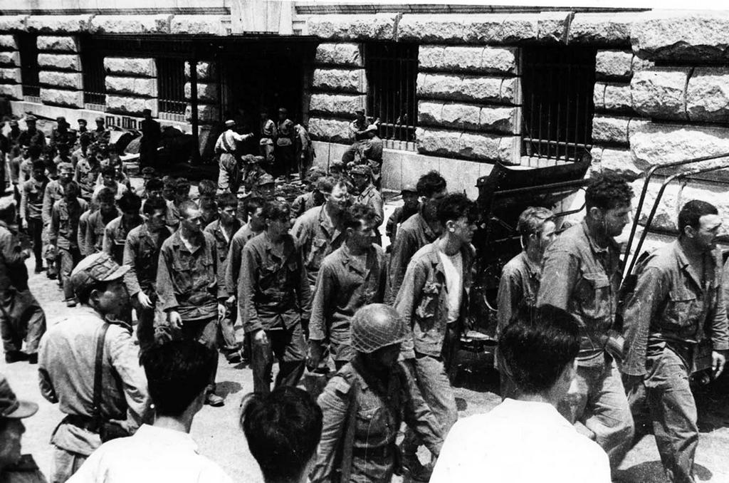 1953_american_prisoners_of_war_march_down_a_street_in_north_korea_following_their_capture_by_communist_forces_during_the_korean_war.jpg