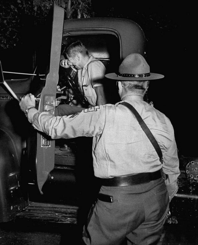 1953_pennsylvania_state_trooper_warns_driver_attempting_to_nap_on_turnpike_shoulder_of_the_presence_of_a_serial_killer_targeting_sleeping_truckers_united_states.jpg