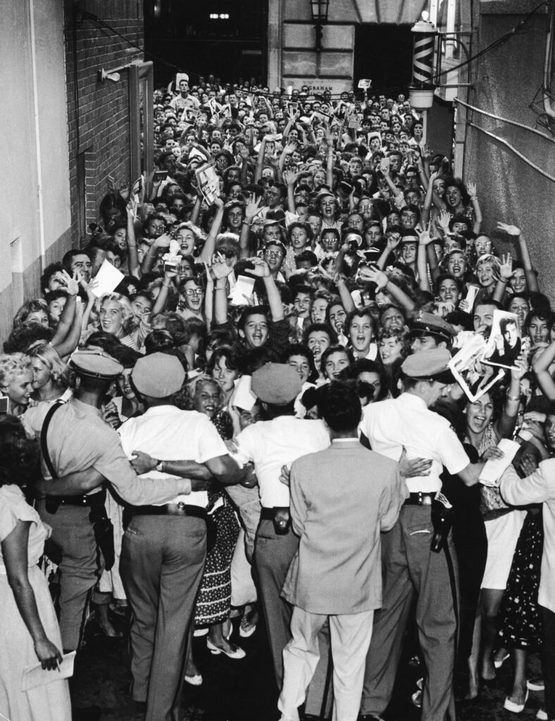 1956_elvis_fans_being_restrained_by_police_outside_of_a_concert_in_florida.jpg