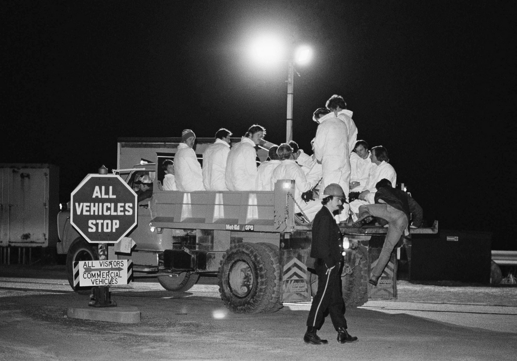 1979_night_shift_workers_wearing_protective_clothing_arrive_at_the_three_mile_island_nuclear_generating_station_aboard_a_flatbed_truck_harrisburg_pa_usa.png