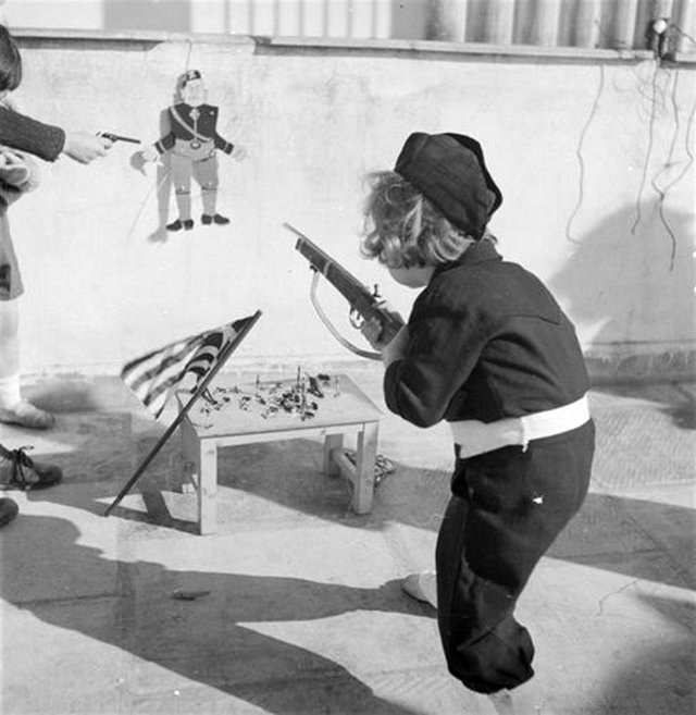 1943_greek_child_shooting_a_toy_gun_at_a_puppet_of_mussolini.jpg