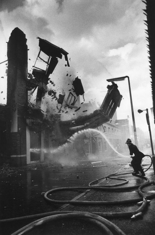 1972_firefighter_putting_the_fire_of_the_aftermath_of_an_arson_attack_presumably_by_the_ira_belfast_ireland.jpg