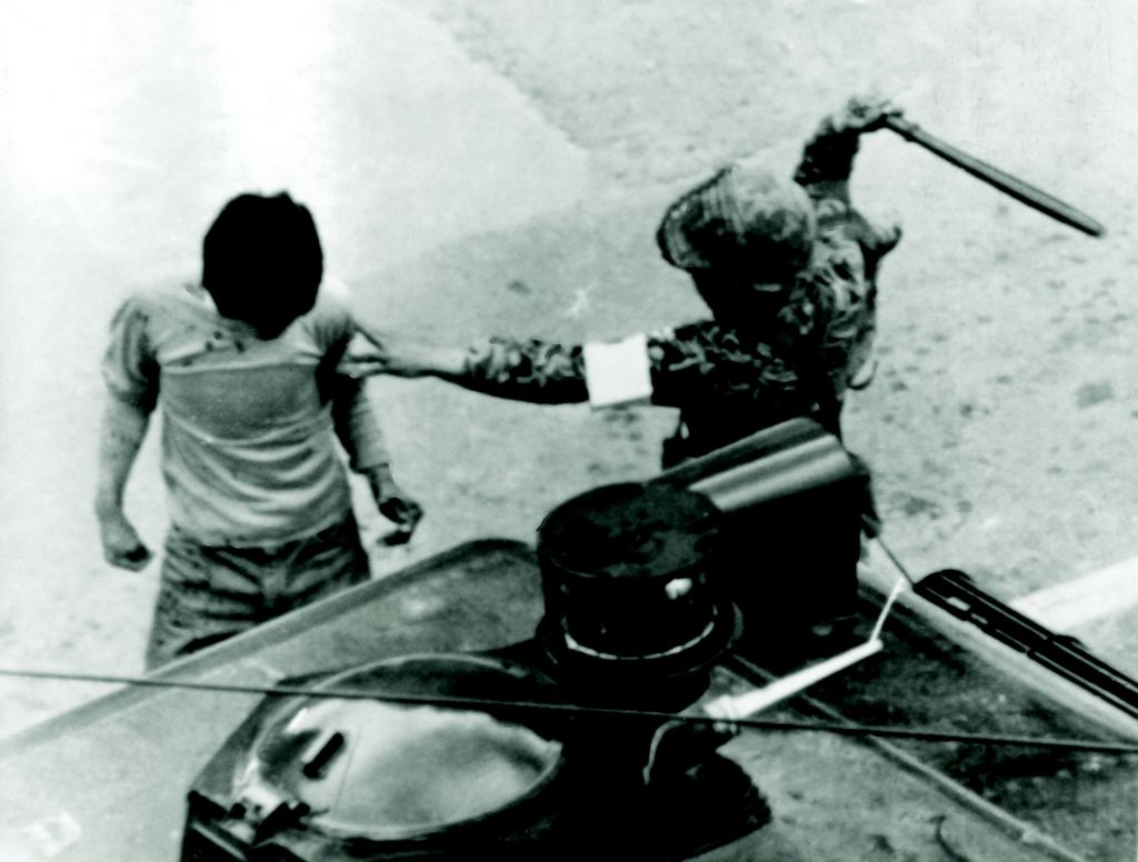 1980_a_south_korean_paratrooper_clubs_a_man_arrested_during_anti-government_protests_in_gwangju.jpg