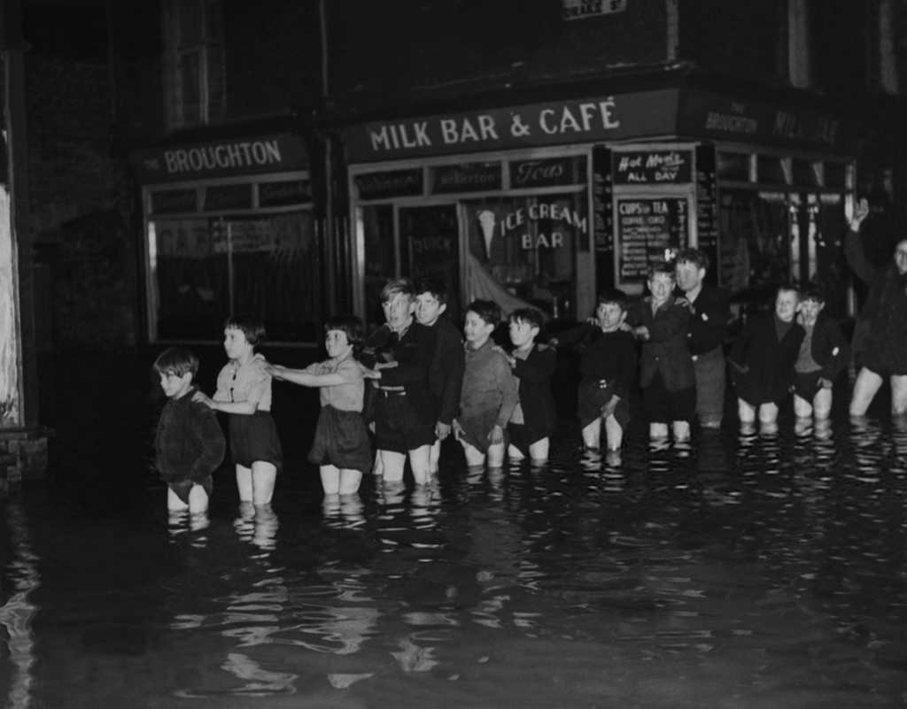 1946_a_group_of_children_watching_the_fun_part_of_the_irwell_river_overflow_lancashire_england.jpg