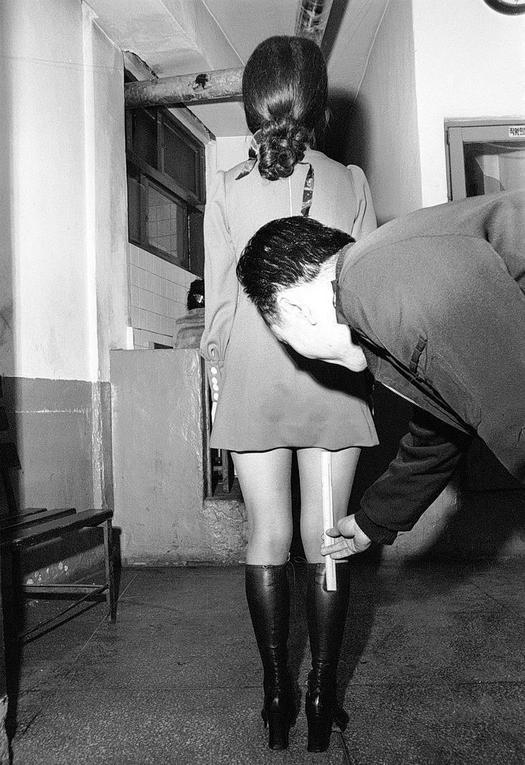 1973_a_south_korean_police_officer_measures_a_woman_s_skirt_length_during_a_nationwide_crackdown_on_men_with_long_hair_and_women_wearing_short_skirts_in_south_korea.jpg
