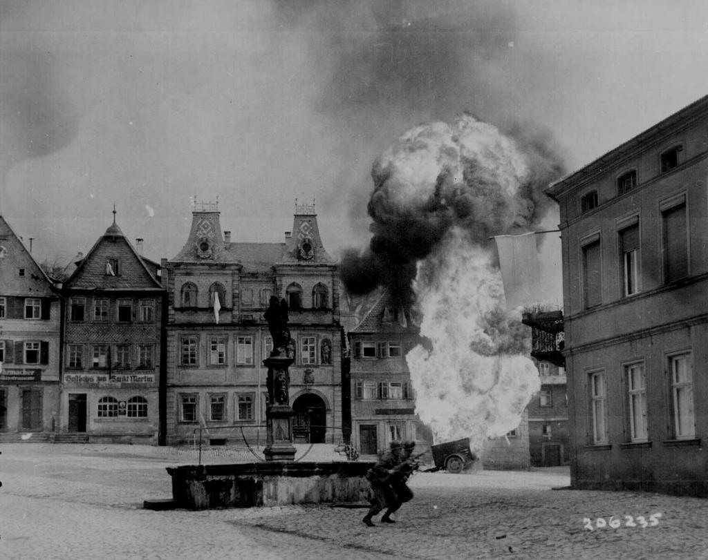 1945_aprilis_14_men_of_us_101st_infantry_regiment_running_past_a_burning_fuel_trailer_in_square_of_kronach_bayreuth_germany.jpg