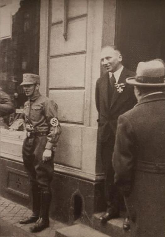 1933_a_german-jewish_ww1_veteran_wears_his_iron_cross_while_a_nazi_soldier_stands_in_front_of_his_shop_for_intimidation.jpg