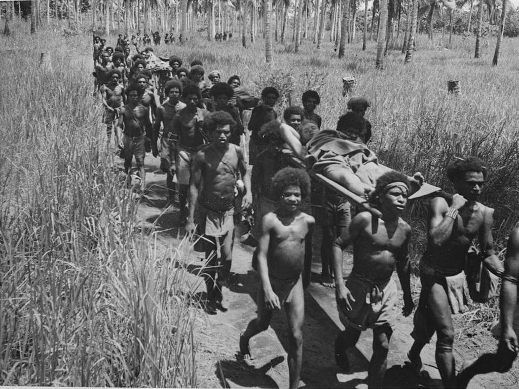 1942_native_villagers_carrying_wounded_allied_soldiers_to_an_american_aid_post_near_buna_new_guinea.jpg