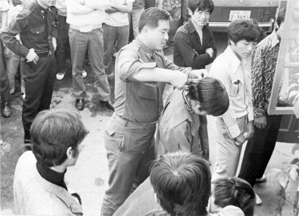 1975_a_south_korean_soldier_forcibly_cuts_a_young_man_s_hair_in_front_of_others_during_a_nationwide_crackdown_on_men_with_long_hair.jpg