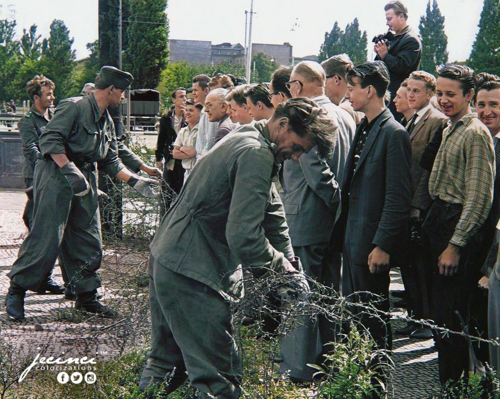 1961_aug_13_east_german_soldiers_set_up_barbed-wire_barricades_at_the_border_separating_east_and_west_berlin_while_west_berlin_citizens_watch.jpg