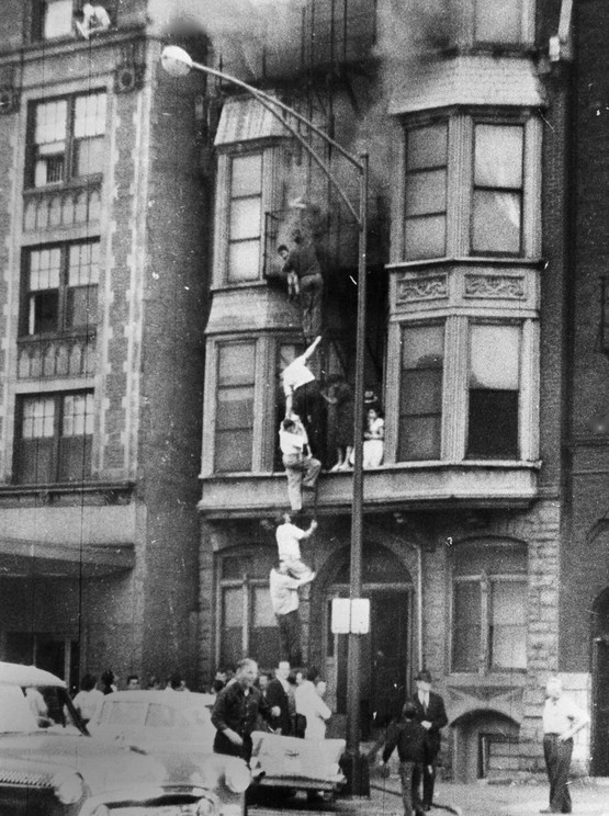 1958_chain_of_people_fleeing_a_fire_descends_a_ladder_fire_escape_as_smoke_pours_from_the_upper_windows_of_the_four-story_building_on_the_north_side_of_chicago_only_one_woman_injured.jpeg