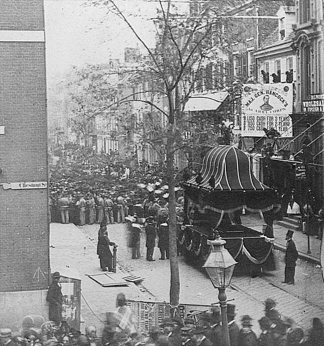 1865. Abraham Lincoln temetési menete Springfieldben. A koporsót szállító lóvontatású járműv sínen haladt végig a város utcáin..jpg
