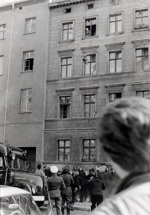 1961_okt_7_a_negy_eves_kelet-berlini_michael_findert_dobja_ki_apja_a_harmadik_emeleti_ablakbol_az_utca_mar_nyugat-berlin_ahol_tuzoltok_haloval_varjak_az_ugrast.jpg