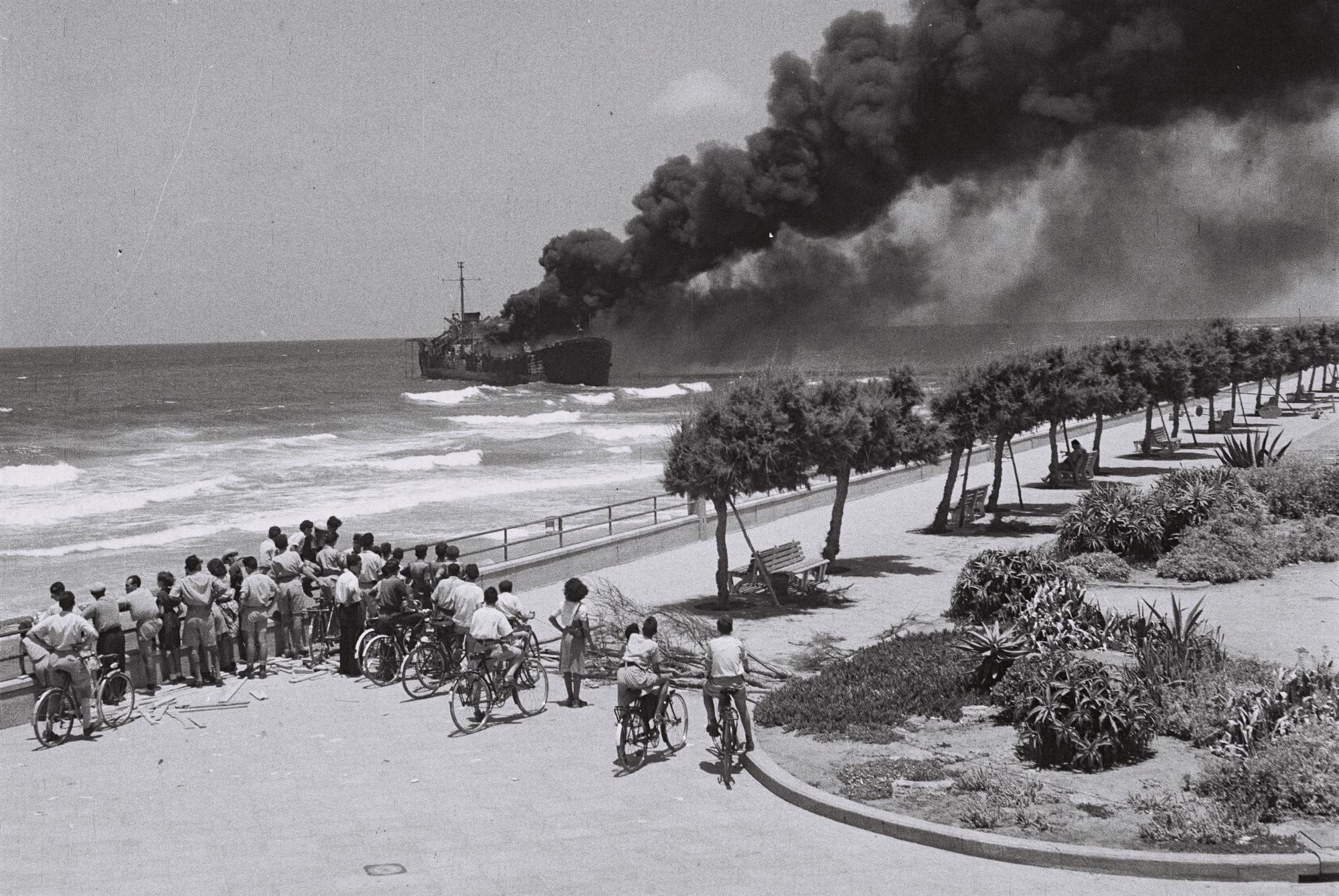 1948. Tel Aviv lakosai nézik az IDF által lebombázott Irgun részére fegyvert szállító teherhajót. A fiatal Izrael legnagyobb belpolitikai nézeteltérése az IDF győzelmével ért véget..jpg