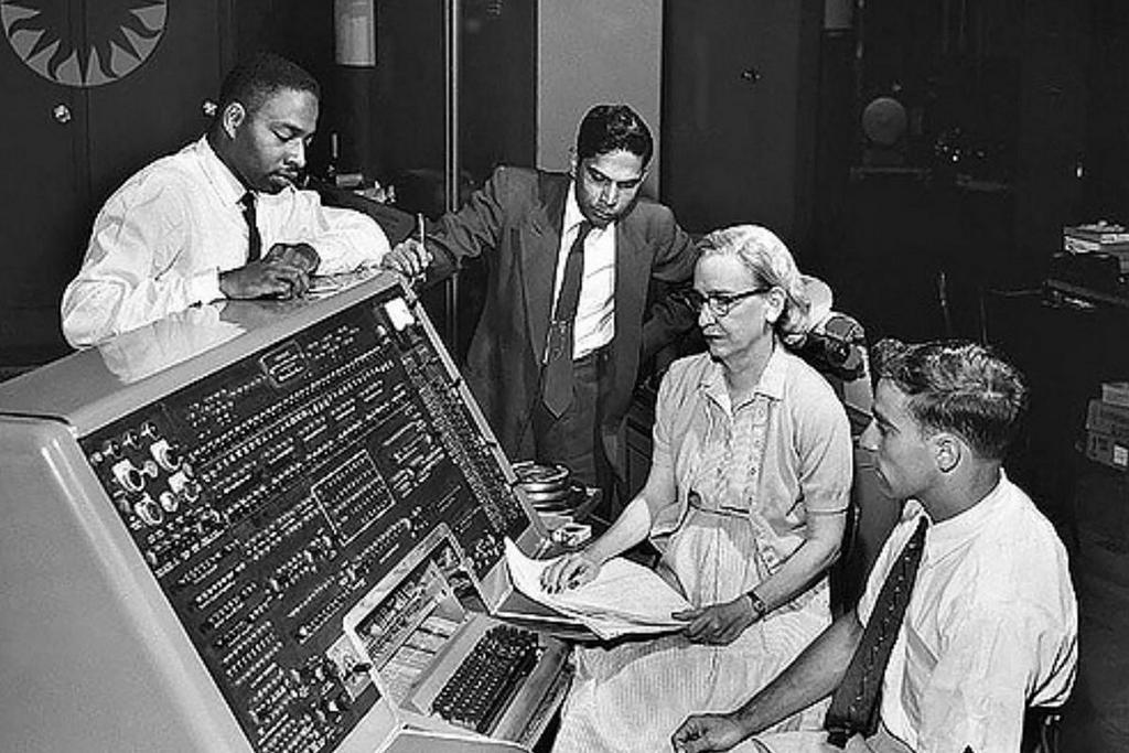 1960_cobol_programmers_donald_cropper_k_c_krishnan_grace_hopper_and_norman_rothberg_with_console_of_univac_i.jpg