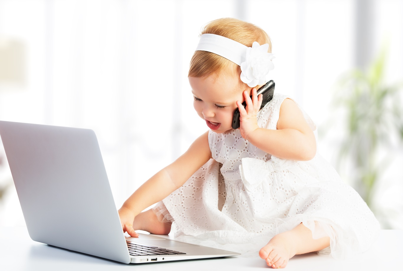dollarphotoclub_58811166-baby-on-laptop-and-phone.jpg