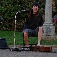 Egy utcazenész lábujjaival játssza el gitáron a 3 Doors Down slágerét
