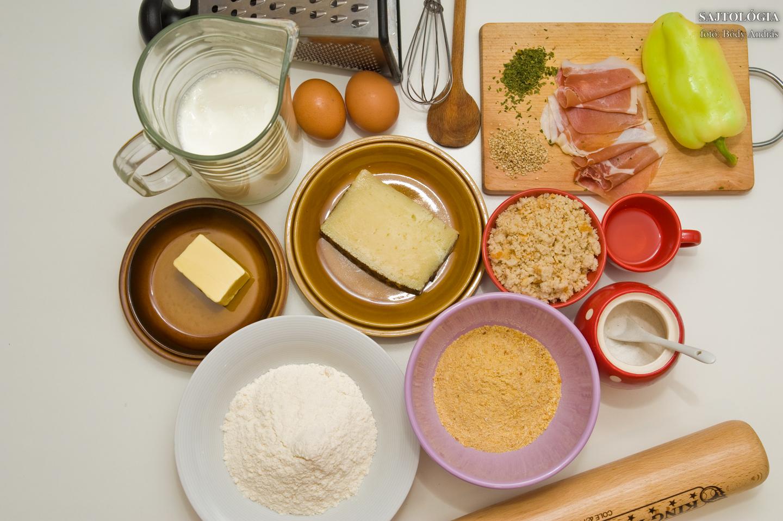 Manchego krokett sonkával és sült paprikával. Hozzávalók: tej, liszt, vaj, só, bors, Manchego sajt, friss kenyérmorzsa, petrezselyemzöld, még egy kis liszt, tojás, szárított zsemlemorzsa (prézli), szezámmag, olívaolaj (nem kell extra), Jamón Serrano, paprika.