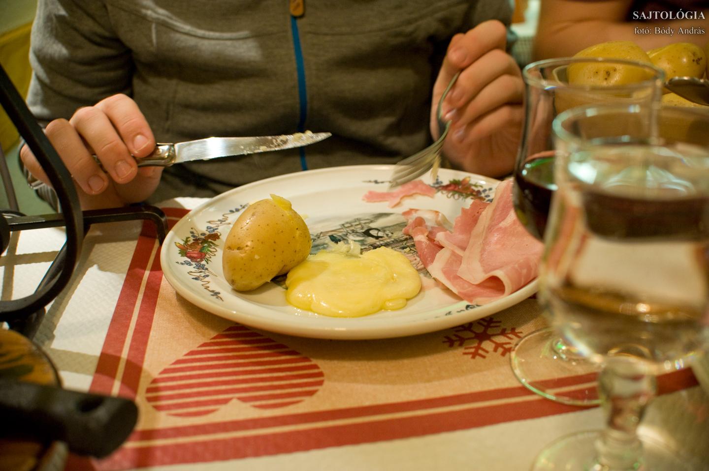 A tányéron: főtt krumpli, felvágott, olvadt Raclette sajt.