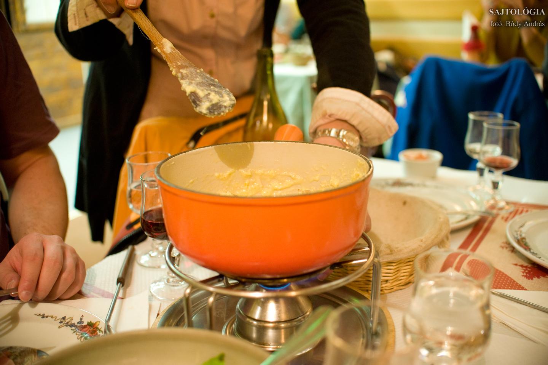 Fondue utolsó fázis: a háziasszony tojást és bagettet habar a sajtos keverékbe.