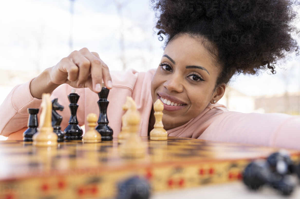 smiling-woman-playing-chess-while-leaning-on-table-jccmf01790.jpg