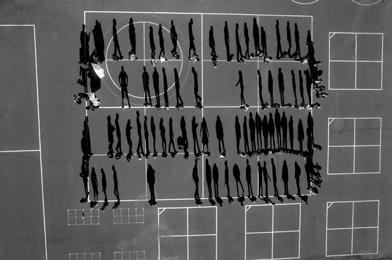 Korunk kérdései<br />3. díj, sorozat<br />Tomas van Houtryve<br />Belgium, VII a Harper's Magazine számára<br />Az Amerikai Egyesült Államok 2002 óta használ drónokat kémkedésre és<br />légitámadásokra Pakisztánban, Jemenben és Szomáliában. A támadások<br />rengeteg halálos áldozatot követeltek, köztük több száz polgári áldozatot. A<br />fotós az Egyesült Államokban olyan események – esküvők, temetések,<br />imádkozó vagy sportoló embercsoportok – fényképezésére használt egy kis<br />drónt, amelyekhez hasonlók a külföldön végrehajtott légicsapások<br />rendszeres célpontjai voltak. Olyan amerikai helyszíneken is készített<br />drónnal fotókat, ahol, rendszeresen használják a drónokat, például<br />börtönökben.<br />Diákok az iskolaudvaron, El Dorado County, Kalifornia. 2006-ban egy<br />drónról tüzeltek a pakisztáni Chenegai falu vallási iskolájára. A híradások<br />szerint akár hatvankilencen is meghalhattak.