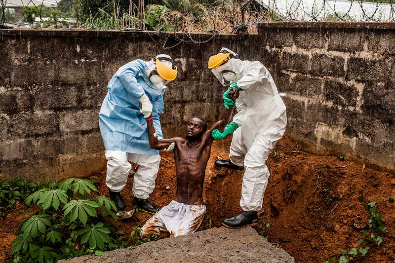 Hír<br />1. díj, sorozat<br />Pete Muller<br />Amerikai Egyesült Államok, Prime a National Geographic / The Washington<br />Post számára<br />A halálos Ebola vírus májusban kezdett ismét áldozatokat szedni Sierra<br />Leonéban. A betegség gyógyíthatatlan, a halálos áldozatok aránya akár a<br />90 százalékot is elérheti. A vírus nagyon fertőző, és rendkívüli<br />óvintézkedésekre van szükség a betegek ápolása és az áldozatok<br />eltemetése közben. Az év végére az Ebola 2758 ember halálát okozta<br />Sierra Leonéban. A kór a szomszédos Guineában és Libériában is<br />pusztított, a három országban összesen 7880 áldozatot követelt 2014-ben.<br />Sírásók pihennek a nap végén a King Tom temetőben Freetownban, Sierra