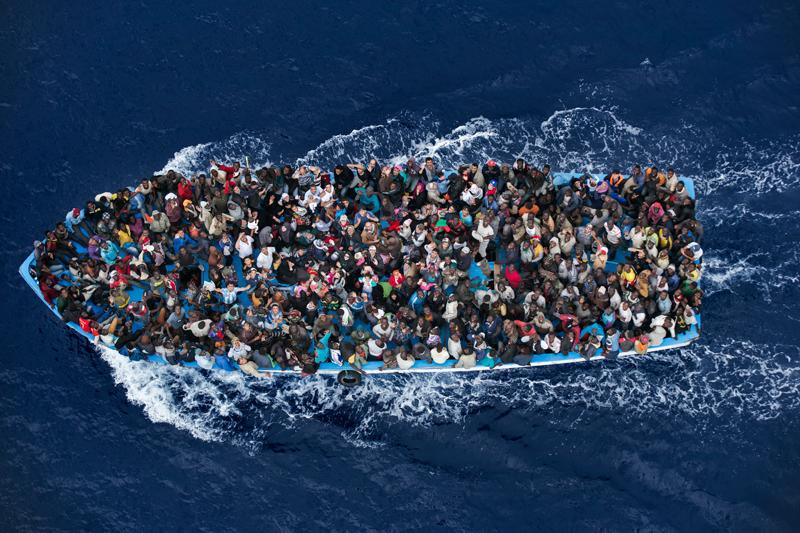 eonéban.<br />Massimo Sestini<br />Hír<br />2. díj, egyedi<br />Massimo Sestini<br />Olaszország<br />Menekültek zsúfolódnak egy hajón körülbelül 25 kilométerre a líbiai<br />partoktól azt megelőzően, hogy a Mare Nostrum művelet keretében<br />megmenti őket egy olasz fregatt. A menekülteket felkutató és megmentő<br />programot az olasz kormány dolgozta ki az után, hogy 2013 végén<br />Lampedusa szigeténél több száz menekült fulladt a vízbe. 2014-ben<br />drámaian megemelkedett azok száma, akik az életük kockáztatásával<br />próbáltak átjutni Olaszországba a Földközi-tengeren. A Mare Nostrum<br />művelet keretében civil szervezetek az életmentésen túl azon is<br />fáradoztak, hogy a menekültek orvosi, kulturális és egyéb segítséghez<br />jussanak. A tengerésztisztek felhatalmazást kaptak az embercsempészek<br />letartóztatására és a hajók lefoglalására. Egyéves működése alatt a Mare<br />Nostrum művelet 330 embercsempészt állított bíróság elé és megmentette<br />több mint 150 000 ember életét – az emberek legalább negyede Szíriából<br />menekült. A Mare Nostrum program októberig működött, akkor felváltotta a<br />Triton, az Európai Unió külső határvédelmi szervezetének, a Frontexnek<br />az irányításával. Ez utóbbi program nem mentő, hanem elsősorban<br />határőrizeti jellegű