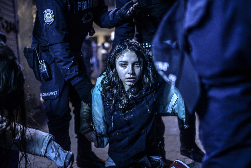 Vezető hír<br />1. díj, egyedi<br />Bülent Kiliç<br />Törökország, Agence France-Presse<br />Egy lány, aki március 12-én sérült meg az összetűzésekben az isztambuli<br />Taksim tér közelében. A 15 éves Berkin Elvan temetési szertartásának<br />résztvevői és a rohamrendőrök csaptak össze. A fiú előző év júniusában a<br />kormányellenes tüntetések idején éppen kenyeret vásárolt, amikor egy<br />könnygázdoboz fejen találta, ez után kilenc hónapig feküdt kómában. A<br />júniusi tiltakozások eredetileg azért kezdődtek, hogy a város Gezi parkját ne<br />építsék be mecsettel és bevásárlóközponttal, aztán országos tiltakozássá<br />fajultak Recep Tayyip Erdoğan miniszterelnök fokozódó egyeduralmi<br />törekvései ellen. Berkin Elvan halála újabb kormányellenes<br />megmozdulásokat váltott ki az egész országban. A folyamatos tüntetések<br />dacára öt hónappal később Erdoğant Törökország elnökévé választották.
