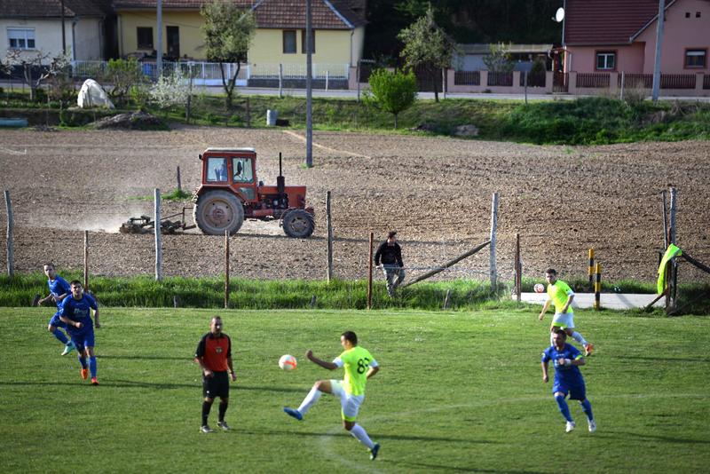 MÁRTONFAI DÉNES: vidéki foci<br />Sokan nem tudják, milyen egy összeeszkábált fapadról buzdítani a rokonunkat, gyermekkori barátunkat, egy aprócska korlát mögül, amit akár mankóval is könnyedén átléphetünk. Teljesen más érzés, mint vasrácsok és betonfalak közt egy stadionban, szektorokba bekerítve. A sport szeretete vidéken másképp nyilvánul meg, mérkőzések hangulata is alapvetően különbözik. Megtapasztalhatjuk milyen a meccs végén, a pálya menti büfében néhány sör mellett, a csapat tagjaival együtt megvitatni, ki és mit hibázott. A férfiak körében társadalmi eseménynek számító alkalomkor, a szurkolók megvitatják a<br />hét történéseit, majd békésen megnézik a mérkőzést. S bár a szurkolói fanatizmus természetesen ilyen alkalmakkor is jelen van, tagadhatatlanul más formában, mint egy nagy, zárt tömbű csarnokban, komoly agressziónak nyoma sincs. S ha a csapat győzelmet arat, annál nagyobb öröm a hűséges szurkoló számára nincs.