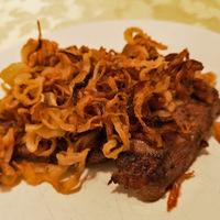 A klasszikus hagymás rostélyos receptje: rengeteg sült hagymakarika takarja be az omlós húst