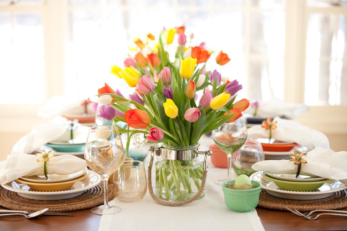 A gyönyörű, tarka tulipánokhoz színes mély- és fehér lapostányérok tartoznak, a terítő - a színeket ellensúlyozva - fehér, az asztal és az alátétek pedig visszafogott barna színűek.