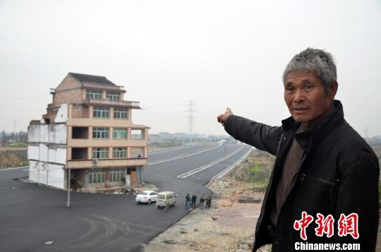 luo-baogen-shows-the-house-sitting-middle-of-road.jpg