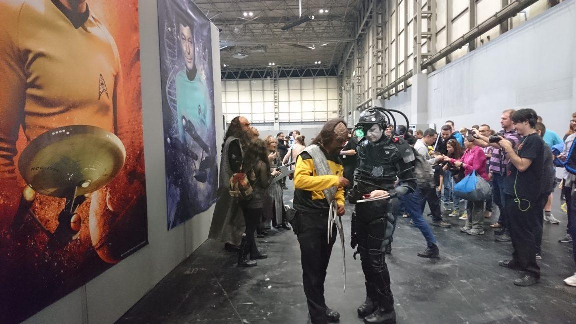 Fajok közti információcsere: Worf útba igazítja a borgot.<br />A háttérben klingonok modellkednek.