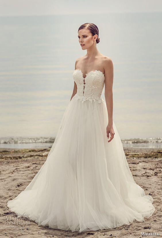 9fb7698359 A menyasszonyi ruhák kizárólag hófehérek, és többségük letisztult, egyszerű  vonalvezetéssel bír. Vannak persze picit fodrosabb, lágyabb esésű ruhák, ...
