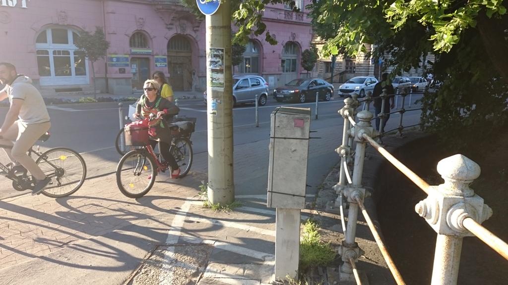 Magyarország legforgalmasabb biciklis csomópontjában úgy gondolták, hogy jó helyen lesz a hídról lendületből lejövő biciklisek útjában ez az aszfalt-színű kapcsolódoboz, így odatették. Sajnos volt, aki már megjárta a klinikát, mire lakossági panaszra körbefestették fehér festékkel, még tovább szűkítve az amúgyis szűk csomópontot.