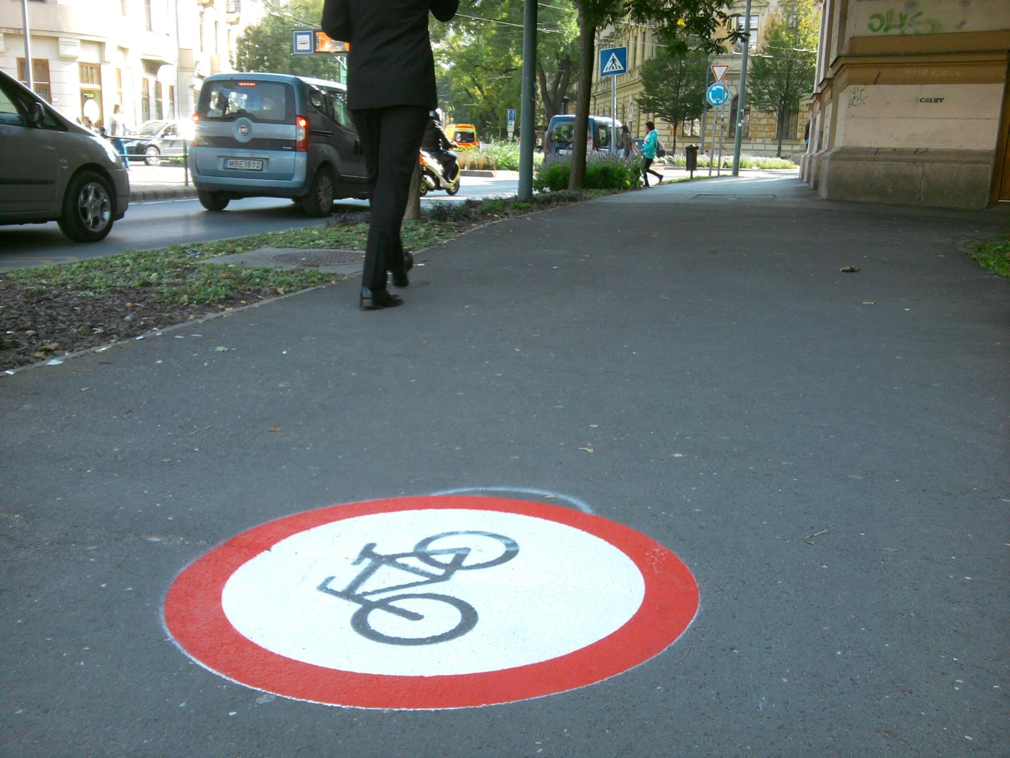 A Dugonics téren úgy gondolták, hogy egy KRESZ táblát végigfestenek a járdán, hátha akkor nem bicikliznek ott az emberek. Igaz, hogy ez semmilyen előírásnak nem felel meg, de legalább azt sugallja, hogy ahol nincs ilyen jelzés, ott szabad a járdán biciklizni. Pedig ez nem igaz, ott sem szabad.
