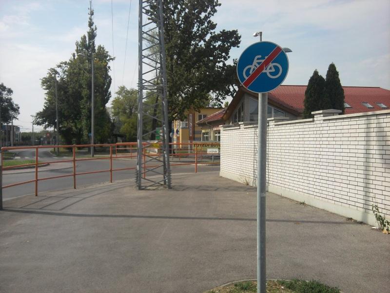 Dova oszlopa a Szabadkai úti körforgalomnál. A bicikliseket egy derékszögű, beláthatatlan kanyarba szorították, és még egy 20 kilovoltos vezetéktartó oszlopot is beletettek a kerékpárút közepébe. Pedig Dova emiatt demonstrált is. A városüzemeltetés megoldotta: megszüntették a kerékpárutat ezen a rövid szakaszon, így mostmár a nyilván továbbra is itt tekerők lesznek a felelősek, nem az, aki ezt az idióta forgalmi rendet összehozta.<br /><br />A demonstráció: http://www.delmagyar.hu/szeged_hirek/villanyoszlopra_maszott_a_nagy_kerekezo/2067490/
