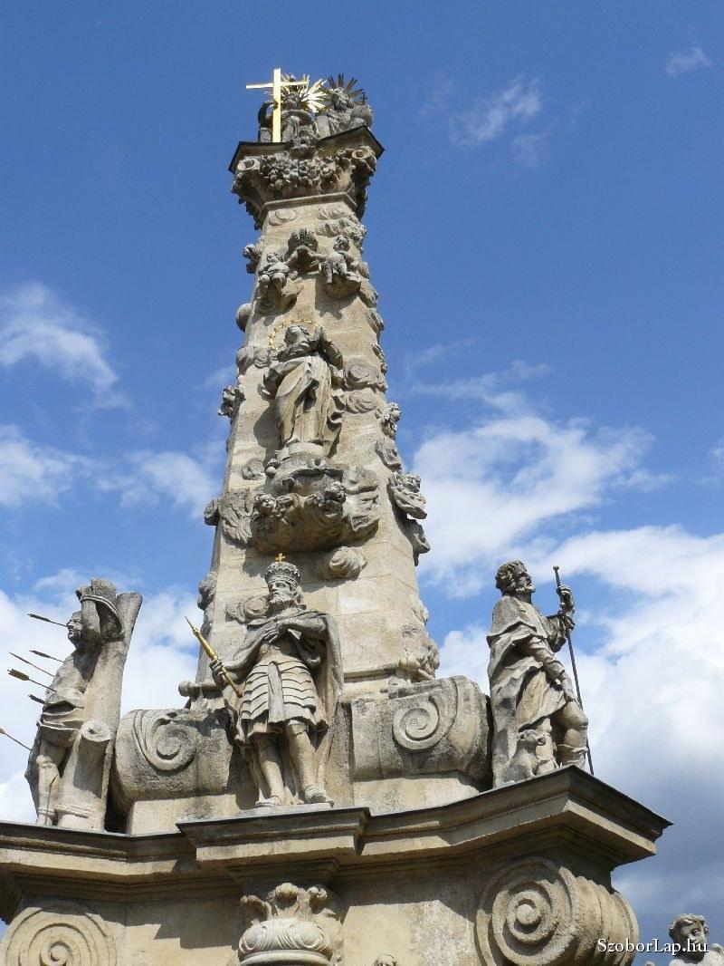 """Kecskemét<br /><br />Kecskeméten a Szentháromság barokk szoborcsoportját az 1739-es pestisjárvány emlékére Conti Lipót Antal készítette 1741-1742-ben. Háttérben a Városháza látható. A szobor a Katona József Színház bejárata előtt található, azaz 150 évvel később mögötte építették fel a színházat!<br /><br />A szöveg így hangzik:<br />""""Annak az évnek emlékére igazságos szent Isten, vedd tieidnek kegyes fogadalmát, s egek hatalmas királya távolítsd el tőlünk a mirigyhalált'.<br />A stilizált felhőpamacsokkal telehintett oszloptörzs magasságának felénél látható puttók társaságában a barokk legjellemzőbb Mária ábrázolása, azImmaculata szobor. Ez általában földgömbön állva, a kígyó képében megjelenő gonoszt eltaposva jeleníti meg a Szeplőtelen Szüzet.<br /><br />Alatta a párkányzatonSzent Istvánalakja látható két oldalán a legnépszerűbb pestissel kapcsolatban álló szenttel,Szent SebestyénnelésSzent Rókussal.<br />Itt kapott helyet továbbáAssisi Szent Ferencszobra is, amit valószínűleg a közelben álló ferences kolostor indokol.<br />"""