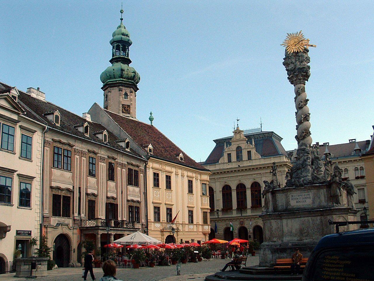 Sopron<br /><br />A soproni Szentháromság-szobrot az 1695-ös pestisjárvány idején állították. AFő térközepén emelkedő barokk alkotást Késmárki Thököly Éva Katalin és férje, Löwenburg Jakab emeltette fogadalmi emlékműként. Az adományozók térdeplő alakjai ott láthatók az adományozásról számot adó latin nyelvű felirat két oldalán.<br /><br />A virágfüzérekkel és puttókkal díszített csavart oszlop lábánál a Szűzanya áll szentekkel körülvéve, a korinthoszi oszlopfőt pedig a Szentháromság koronázza.