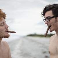Péter és Simon a tengerparton szivarra gyújt