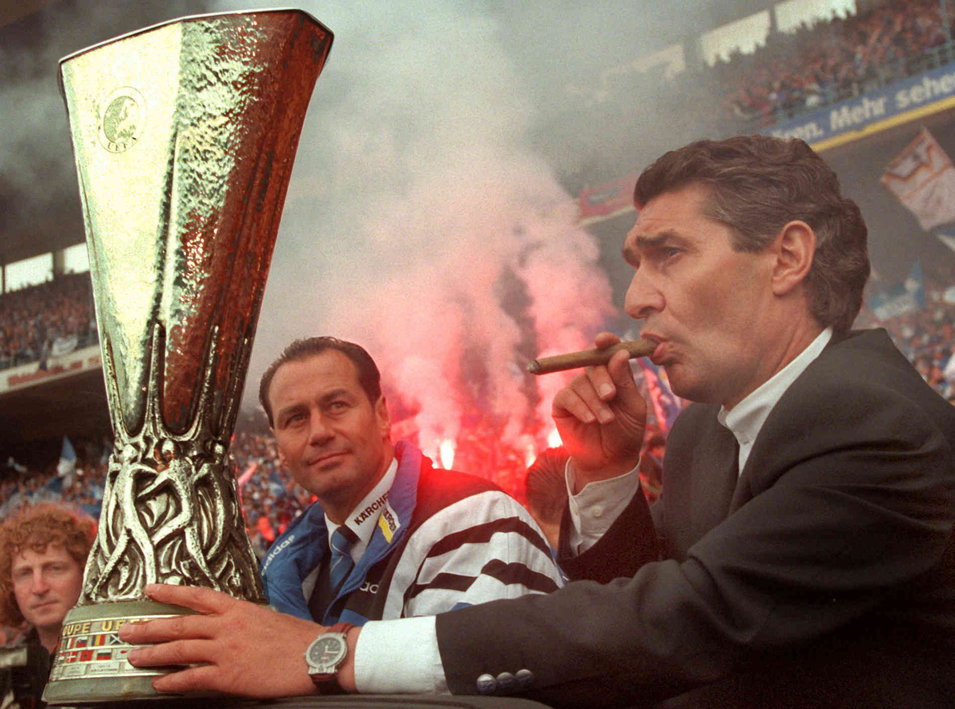 fc_schalke_04_manager_rudi_assauer_is_puffing_smoke_from_his_cigar_shortly_before_the_match_-cigarmonkeys_com_cigar_sport_style_1.jpg
