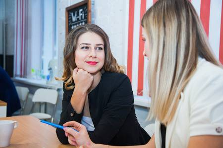 two-girlfriends-sit-together-talk-discuss-smile-young-women-meet-at-working-place-for-freelancers-.jpg